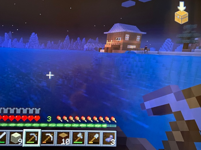 Screenshot from Minecraft, which shows a house on the edge of the sea, as viewed from a boat out on the water. And Enderman stands close to the house, with his pinkish-purple eyes glowing in the distance.