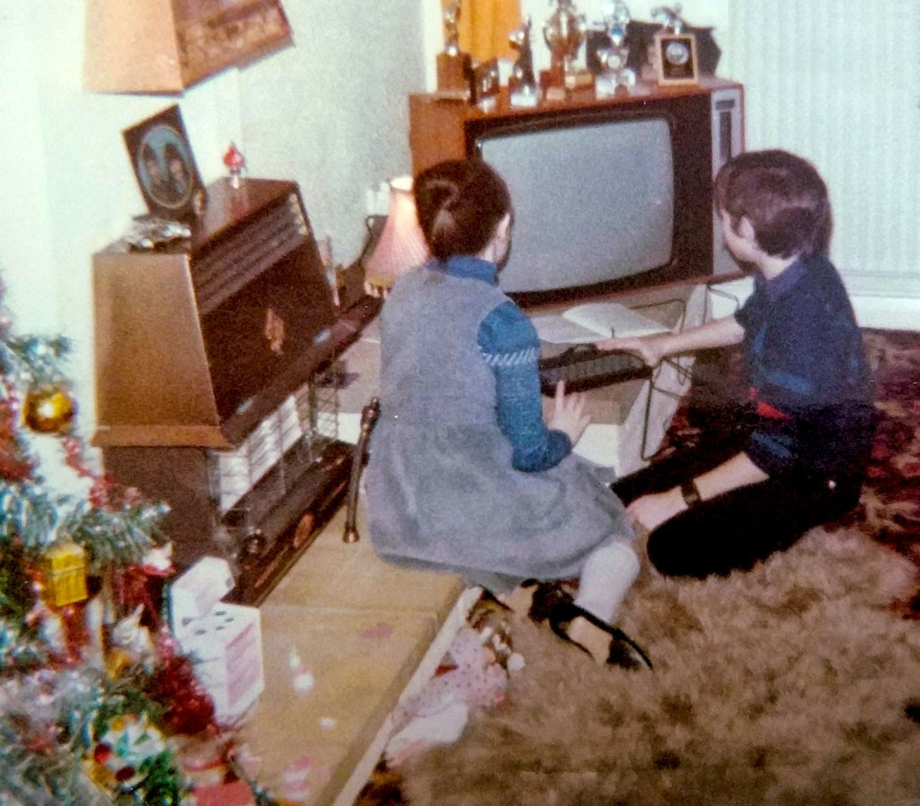 My sister and I sitting in front of the television on Christmas Day 1984, with a ZX Spectrum 48k in front of us. The edge of a Christmas tree, covered in baubles and decorations, in the foreground.