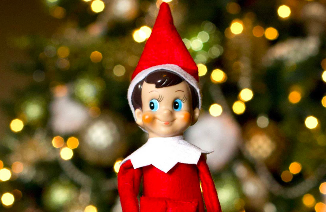 The Elf on the Shelf smiling and looking cheeky, with the lights of a Christmas tree blurred in the background.