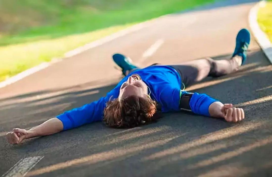 A male runner on his back, collapsed on the pavement.