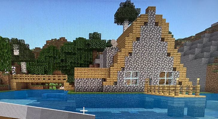 A lakeside cabin in Minecraft with a wooden A-shaped roof and a little jetty.