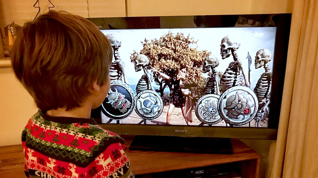 Young boy standing in front of the TV watching Jason and the Argonauts