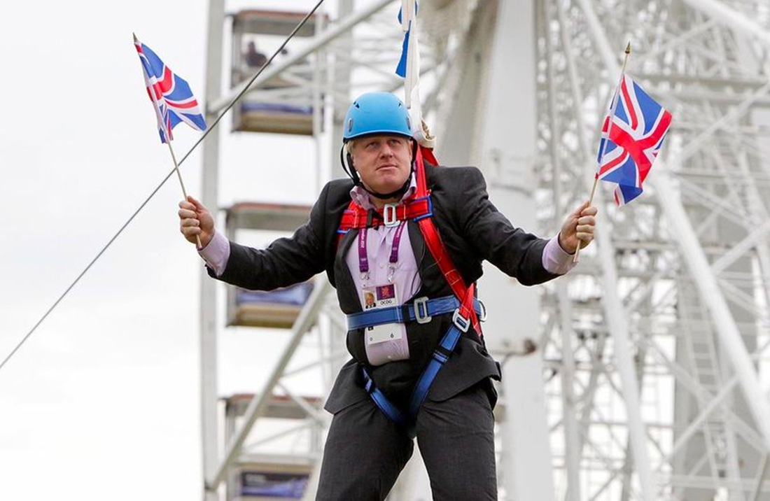 Boris Johnson waving two union flags while stuck on a zip line